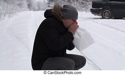 Stressful man breathe into paper bag near car on snowy road