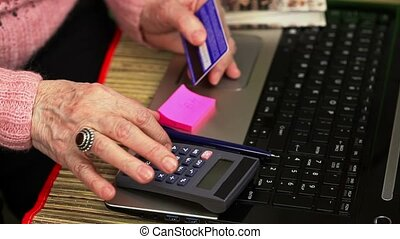 Woman with calculator to counting near laptop