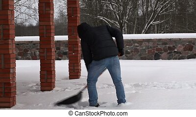 Teenager using snow shovel in winte