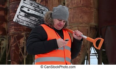 Man with cell phone and snow shovel
