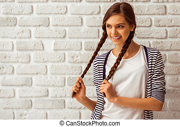 Cute teenage girl in casual clothes playing with her braids,...
