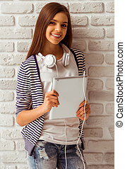 Cute teenage girl in casual clothes standing with a tablet...