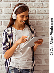 Cute teenage girl in casual clothes using a tablet,...
