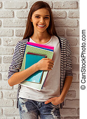 Cute teenage girl in casual clothes holding books, looking...