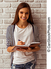 Cute teenage girl in casual clothes making notes in a...