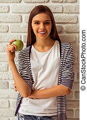 Cute teenage girl in casual clothes holding an apple,...