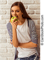 Cute teenage girl in casual clothes eating an apple, looking...