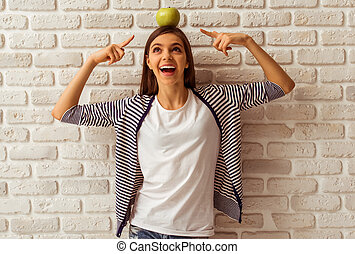Cute teenage girl in casual clothes standing with an apple...