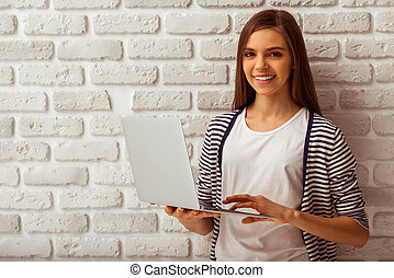 Cute teenage girl in casual clothes holding a laptop,...