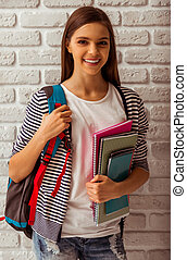 Cute teenage girl in casual clothes standing with a school...