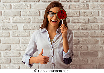 Cute teenage girl in sunglasses holding a lollipop, showing...