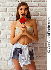 Cute teenage girl in a top and shorts holding a lollipop,...