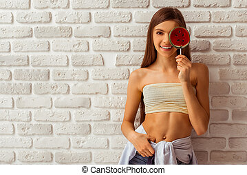 Cute teenage girl in a top and shorts covering one eye with...
