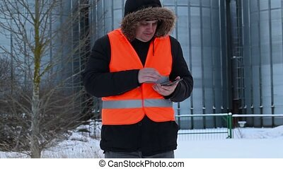 Engineer numbering with tablet PC near tanks in winter