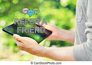 Refer A Friend concept with young man holding his tablet...