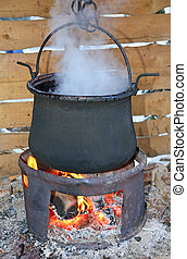big black pot with the fire lit and the dense white smoke...