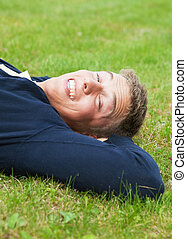Leisure time - Young blond guy lying on grass, slit eyes...