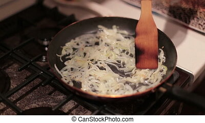Hands female stirs onions for frying in a pan to cook dinner...