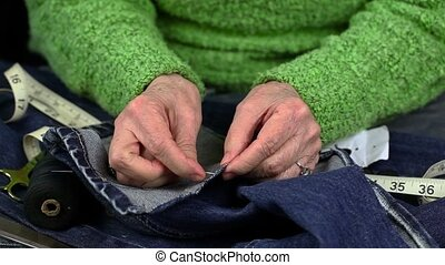 Woman with needle and thread and denim fabric