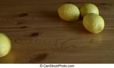 Lemon rolling to three lemons on a wooden table. Slow motion