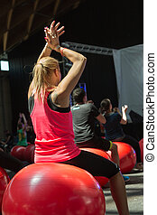 Blonde Young Girl doing Fitness Activity Sitting on Big Red Ball