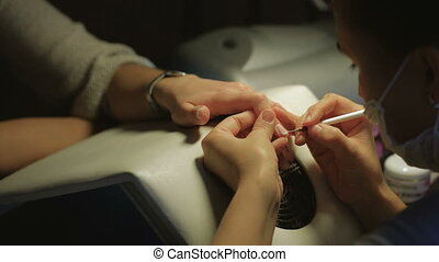 Woman in a nail salon receiving manicure by a beautician....