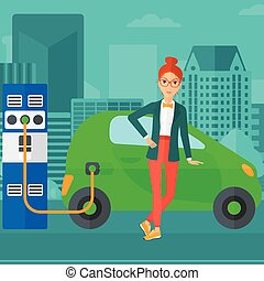 Charging of electric car - A woman charging her electric car...