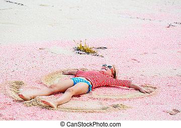 Girl making sand angel - Little girl making sand angel on...