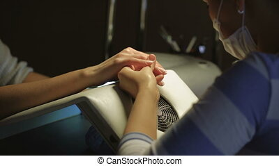 Manicure process in beauty salon showing filling and polishing of nails.