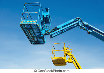 Two crane's baskets against clear sky. Lifters in blue and...