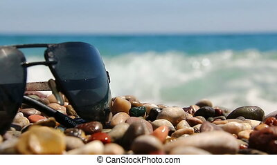 Sunglasses on a pebble beach by the sea