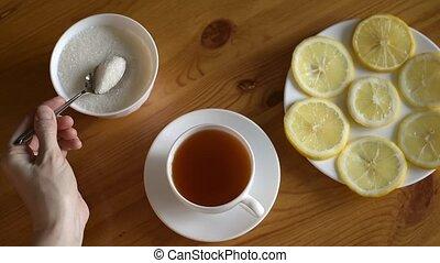 Putting sugar and lemon into tea