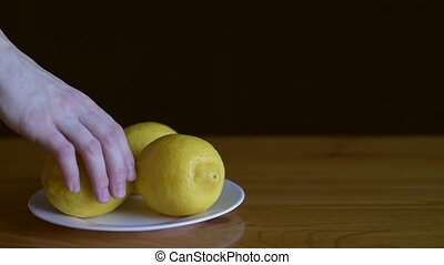 Taking lemons away and putting them back on a wooden table