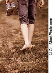 Unidentifiable person walking barefoot on trail - Rear close...
