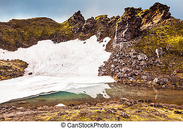 Big unmelted in July snowfield reflected in water. Summer...