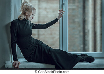 Woman lying on the window sill and sad. - Blonde woman lying...