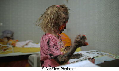 A small girl with paint all over her face. Black and red...