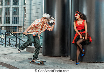 Old grandfather rushes on a skateboard He had a stick in his...