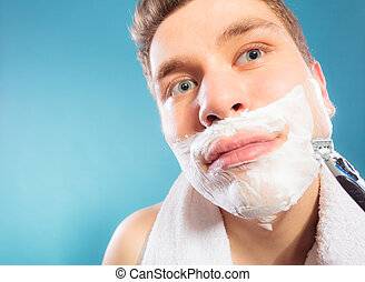 Man shaving using razor with cream foam.
