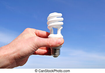 Hand Holding a Compact Fluorescent Light CFL Against a Blue...