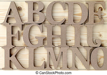 wooden alphabet blocks with letters, on wood background