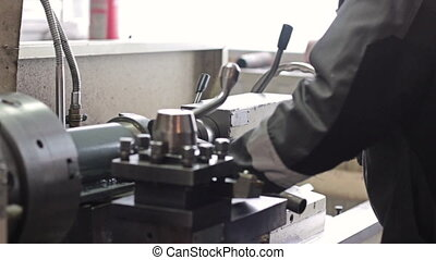 Employee drilling in flat steel plate with bench drill -...