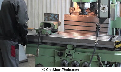 Worker on a machine metal lathe in factory. Machining...
