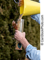 Food for birds is added into a birdfeeder - Birdfeeder is...