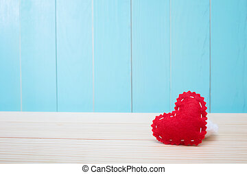 Hand crafted felt heart on blue background