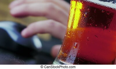 man drink fresh beer with foam in front of mouse and pc...