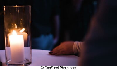 Close-up picture of female hands applauding at the night event. Woman sitting at the table with a firing candle on it.