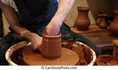 Potter working with clay in pottery - Professional potter...