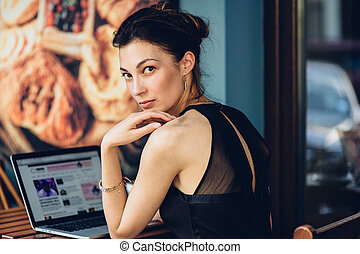 Attractive business woman working at his laptop in a cafe on...