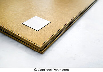 Abstract gold leather menu covered, on white marble stone...